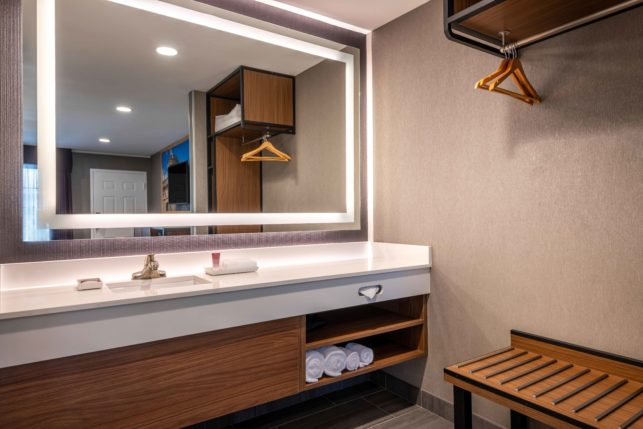bathroom vanity with custom bath amenities and LED mirror