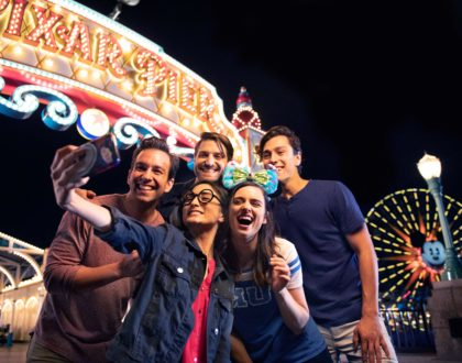 Group of teen boys and girls taking a selfie in front of ferris wheel at California Adventure