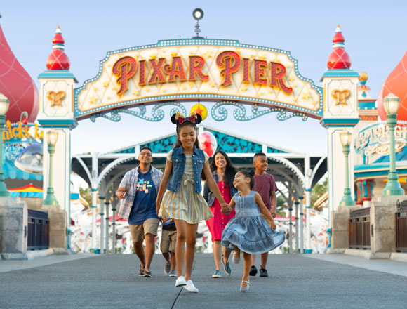 a girl and her family skipping through Pixar Pier