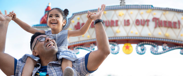 father holding young daughter on his shoulders in front of pixar pier sign